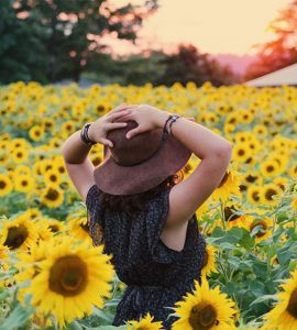 woman standing on a field of sunflowers