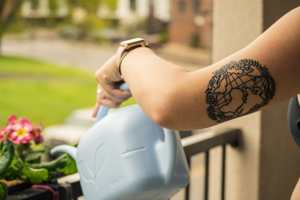 person holding watering can