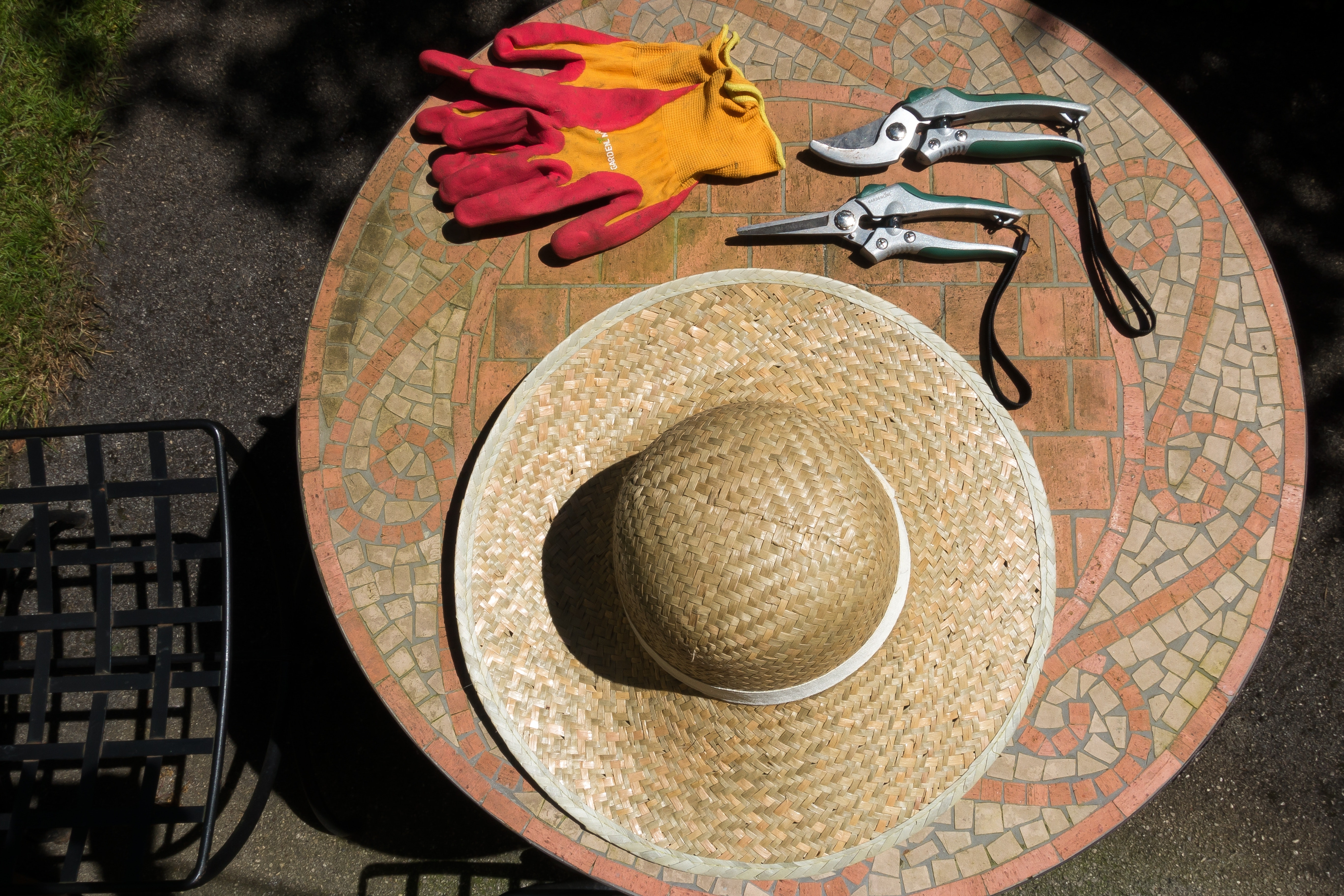 brown hat at the top of round table with garden scissors