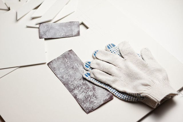 sandpaper and white gloves at the top of plywood
